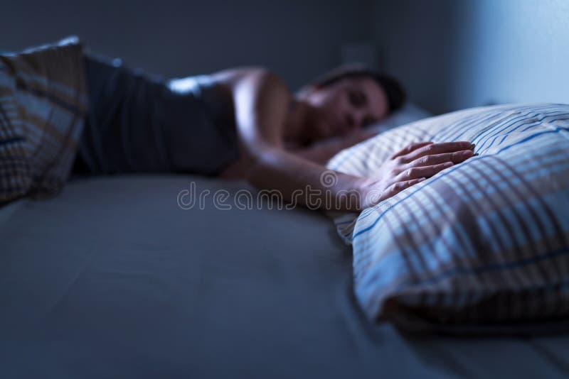 在家单独睡觉在床上的单身妇女 孤独的夫人缺掉丈夫或男朋友 在枕头的手 免版税库存图片