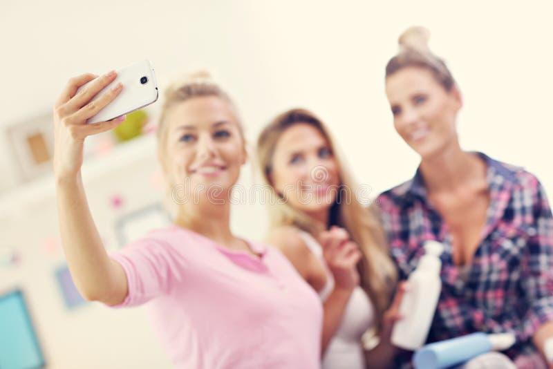 在家变冷和采取selfie的三个美丽的少妇 库存照片