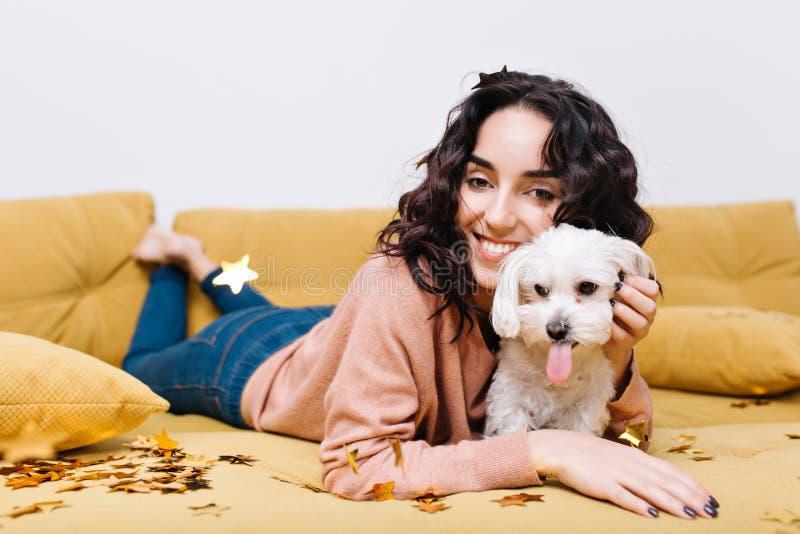 在家变冷在长沙发的愉快的年轻女人的滑稽的国内片刻有家养的宠物的 获得乐趣,金黄闪亮金属片 库存图片