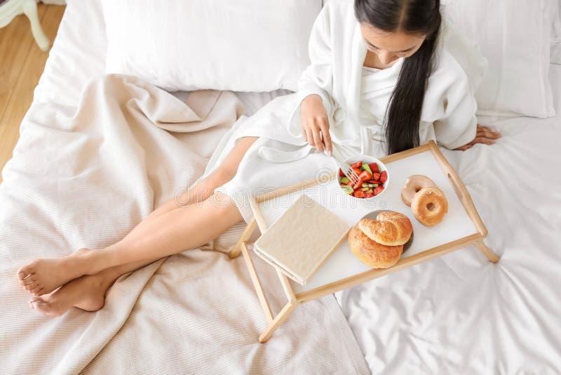 在家吃健康水果沙拉和酥皮点心早餐的亚裔妇女 免版税图库摄影