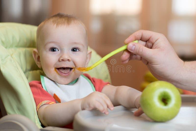 在家吃健康食物在父亲帮助下的婴孩 免版税库存图片