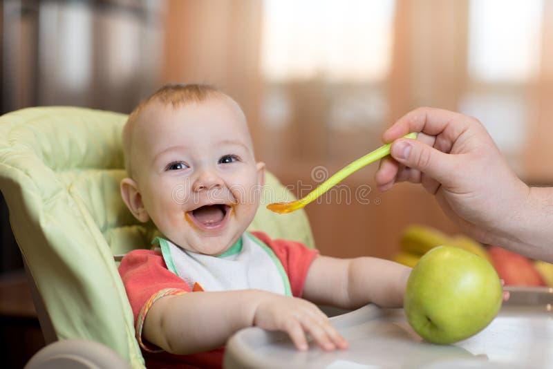 在家吃健康食物在父亲帮助下的婴孩 免版税图库摄影