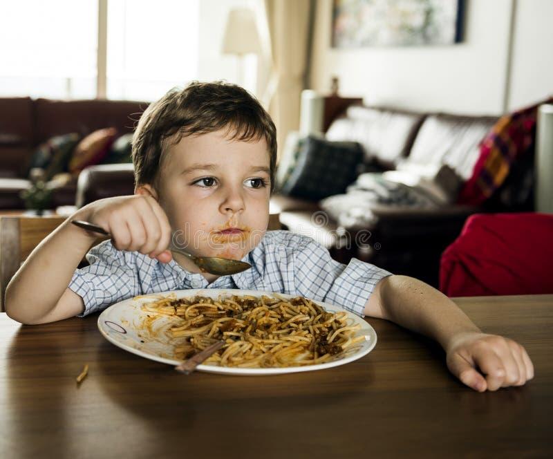 在家吃意粉的男孩进餐时间 免版税库存图片