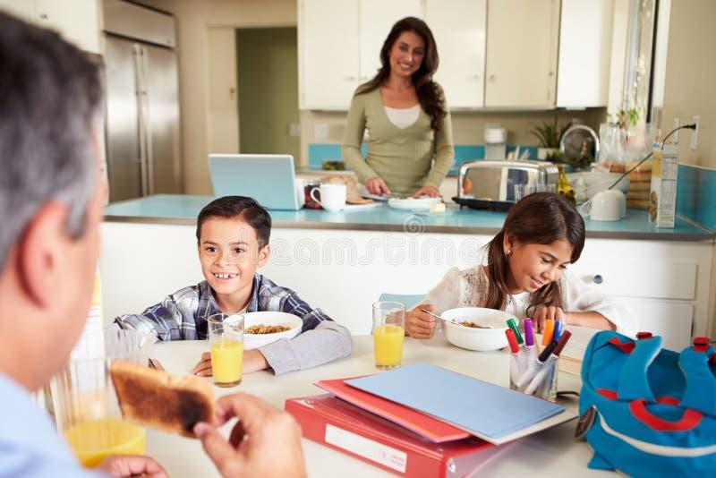 在家吃早餐的西班牙家庭在学校前 免版税库存图片