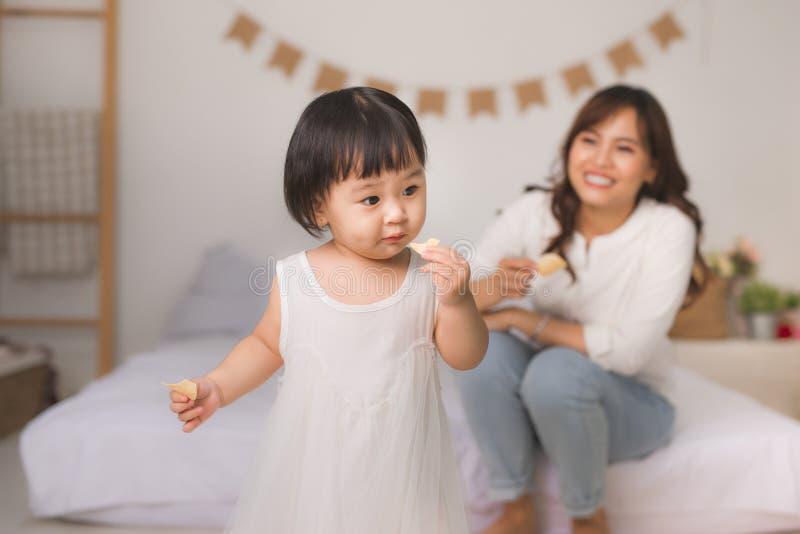 在家吃曲奇饼的逗人喜爱的小女孩 库存照片