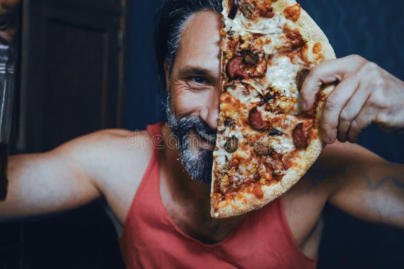 在家吃比萨和喝酒精的残酷有胡子的人 库存图片
