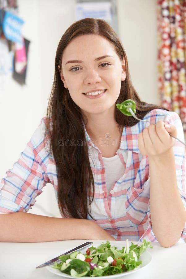 在家吃沙拉的健康板材十几岁的女孩 免版税库存图片