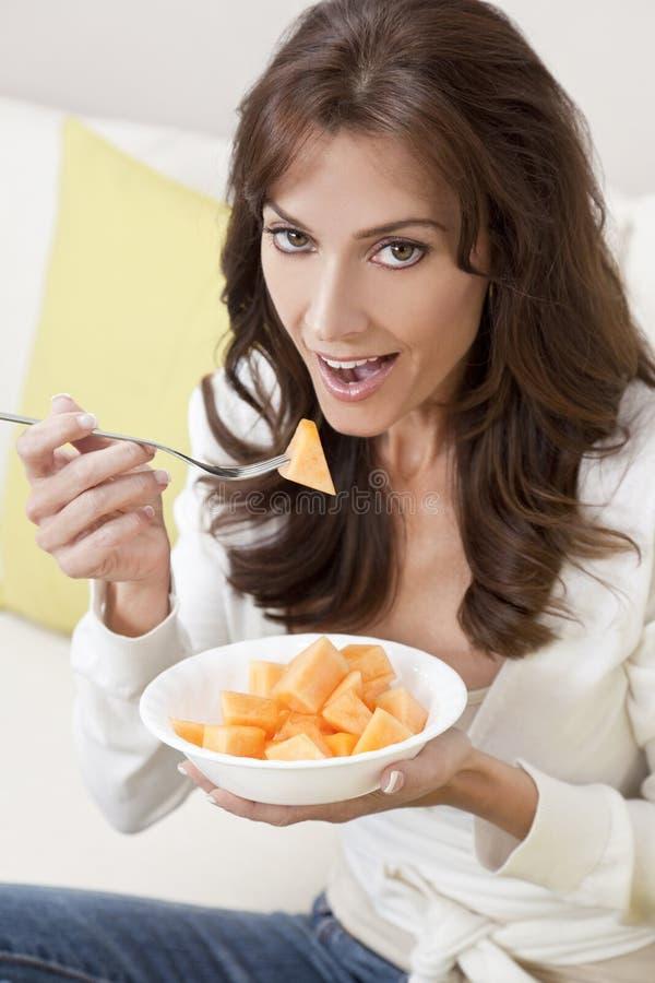 在家吃瓜在沙发的深色的妇女 免版税库存照片