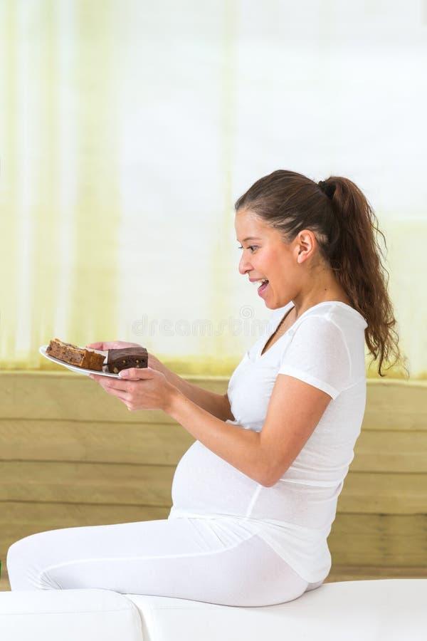 在家吃甜蛋糕的年轻亚裔孕妇 免版税库存图片