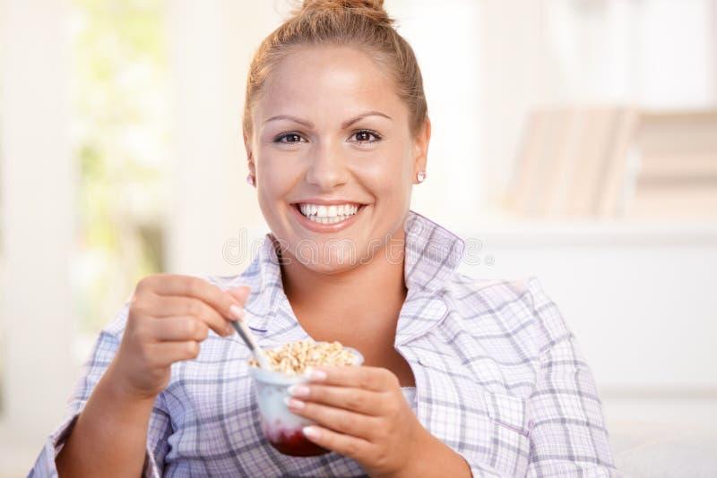 在家吃酸奶的俏丽的女孩节食微笑