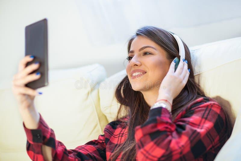 在家听到从片剂的音乐的女孩 免版税库存图片