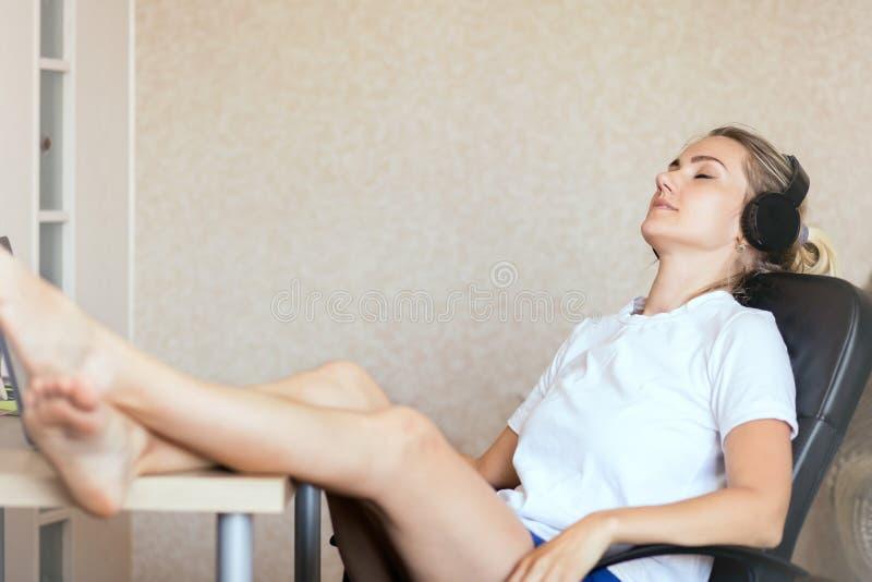 在家听到在耳机的音乐的美丽的白肤金发的女孩 免版税库存照片