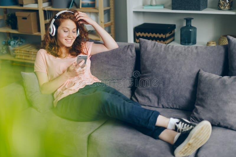 在家听到音乐的微笑的女孩通过耳机使用智能手机 库存图片