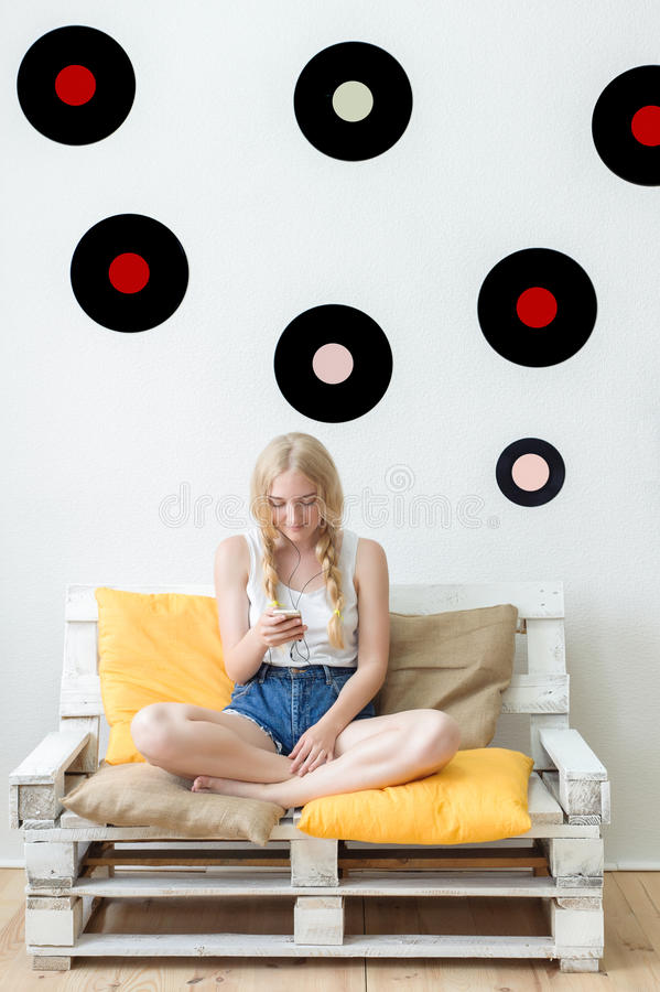 在家听到音乐的美丽的女孩坐c 库存照片