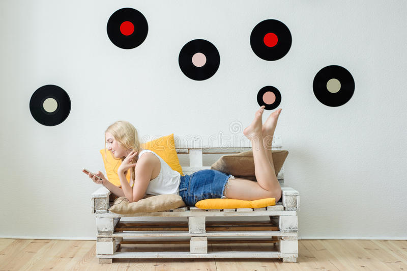 在家听到音乐的美丽的女孩坐c 免版税库存图片