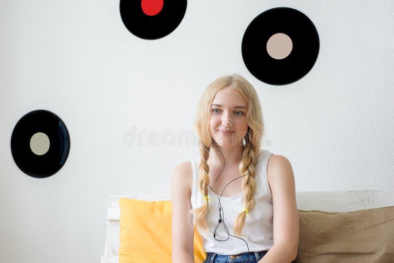 在家听到音乐的美丽的女孩坐c 免版税库存照片