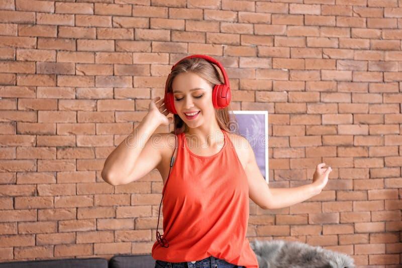 在家听到音乐的美丽的年轻女人 免版税库存照片