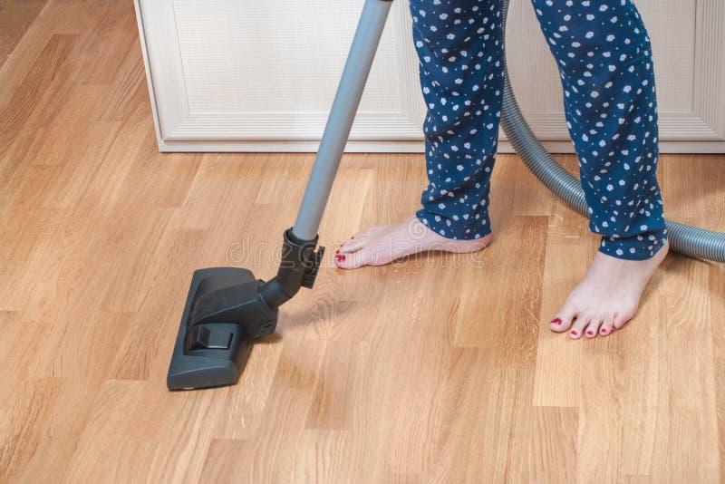 在家吸尘在有吸尘器的屋子里的女孩 接近有修脚的妇女腿在家庭裤子 家事概念 库存图片