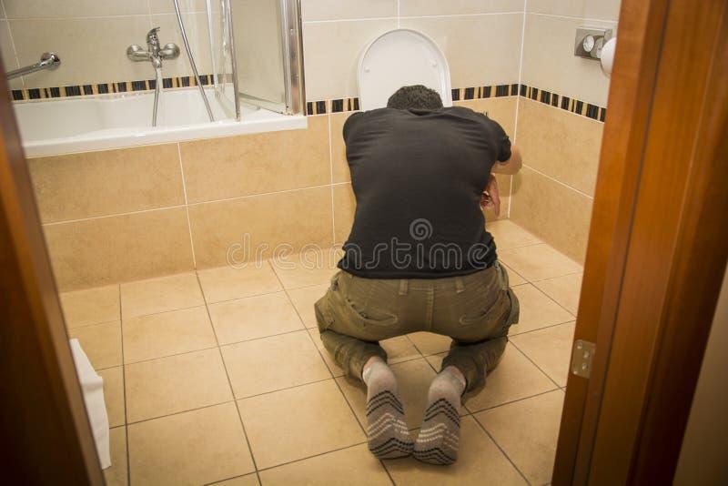 在家呕吐在洗手间的醉酒的年轻人 免版税库存图片