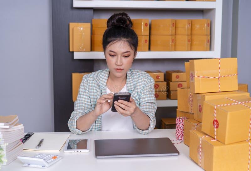 在家和检查产品命令的妇女与智能手机一起使用 库存照片