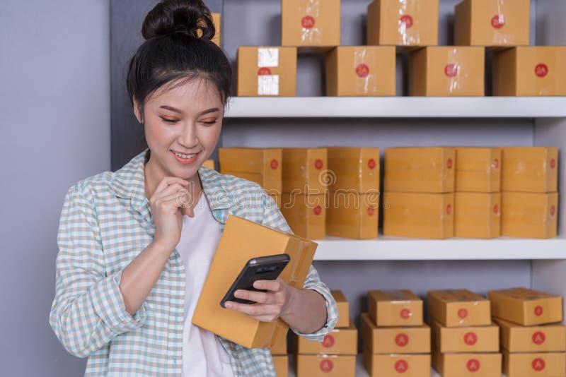 在家和检查产品命令的妇女与智能手机一起使用 库存图片