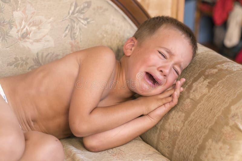 在家哭泣在长沙发的沮丧的小男孩 特写镜头哭泣在沙发的射击了一个哀伤的小男孩 免版税库存照片