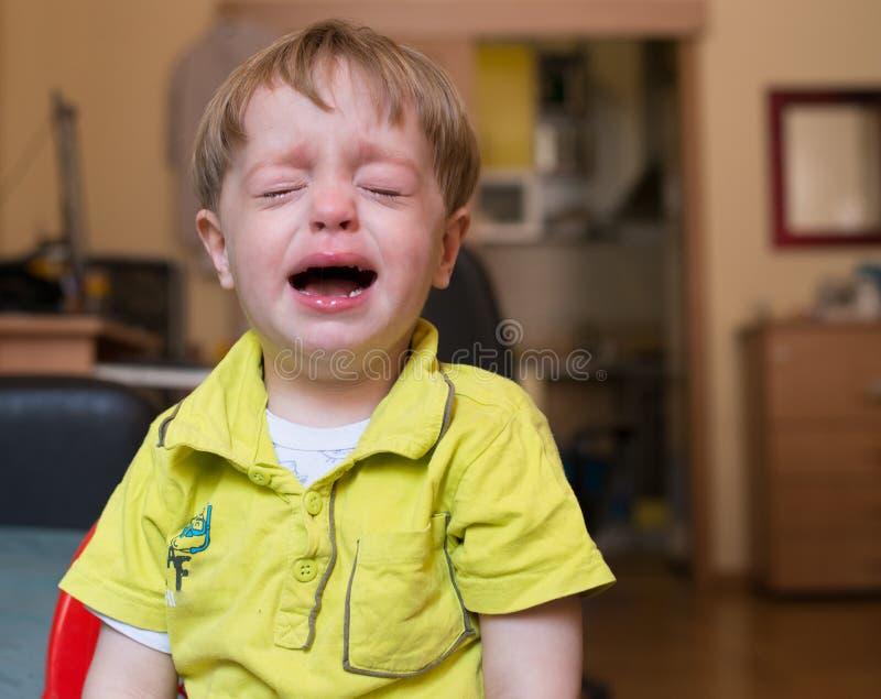 在家哭泣的小男孩 库存照片
