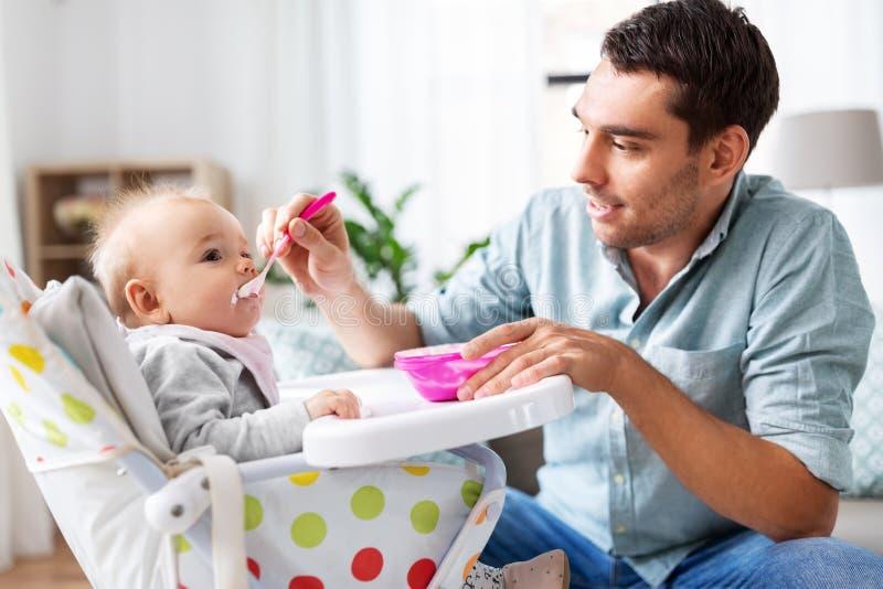 在家喂养高脚椅子的父亲愉快的婴孩 免版税图库摄影
