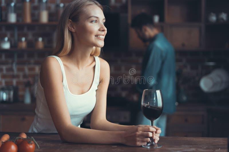在家喝一些酒的俏丽的妇女在厨房里 库存图片