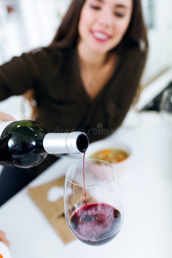 在家喝一些酒的美丽的少妇 免版税图库摄影