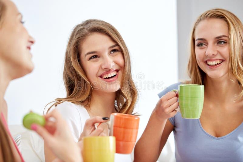 在家喝与甜点的愉快的少妇茶 库存图片