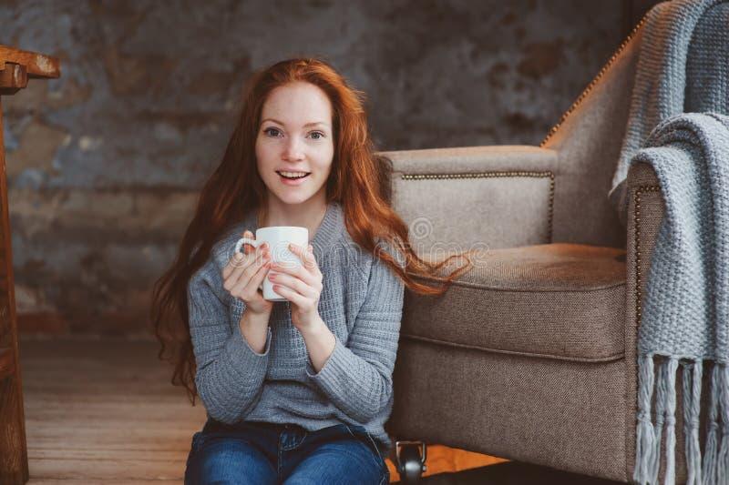 在家喝热的咖啡或茶的愉快的年轻readhead妇女 镇静和舒适周末在冬天 免版税库存图片