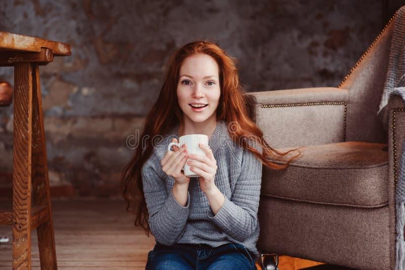 在家喝热的咖啡或茶的愉快的年轻readhead妇女 库存图片