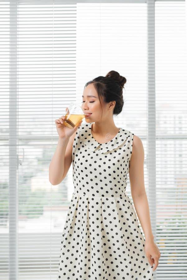 在家喝热的茶的年轻可爱的亚裔妇女 库存图片