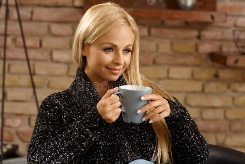 在家喝热的茶的白肤金发的妇女 免版税库存照片