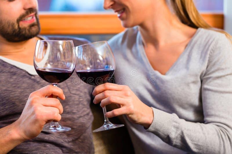 在家喝红葡萄酒的英俊的夫妇 免版税库存照片