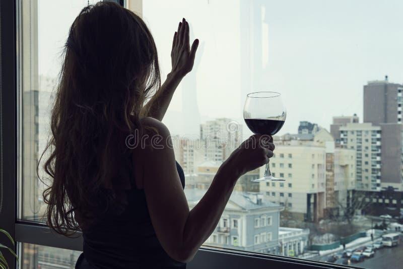 在家喝酒精的孤独的年轻女人 E 黑礼服的单身豪华美女用酒 库存照片