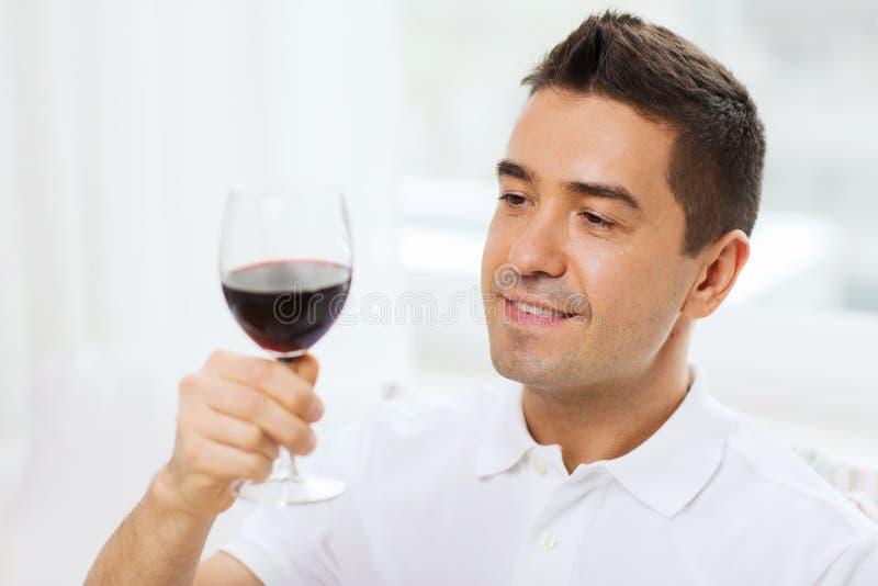 在家喝从玻璃的愉快的人红葡萄酒 库存照片