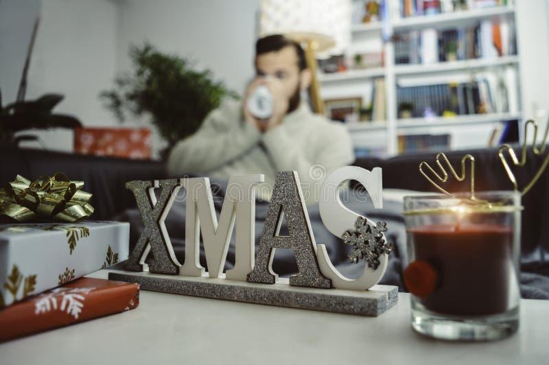 在家圣诞装饰礼物和蜡烛坐长沙发喝单独的地方热的饮料的年轻人 免版税图库摄影