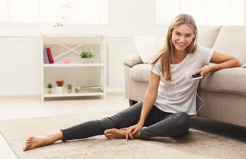 在家在家听到音乐的微笑的女孩 免版税库存照片