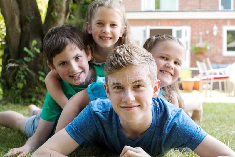 在家在庭院里的四个兄弟和姐妹画象  免版税库存图片