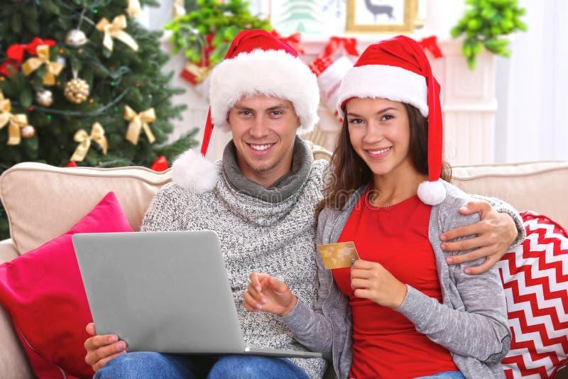 在家在网上购物与信用卡的年轻夫妇圣诞节 免版税库存照片