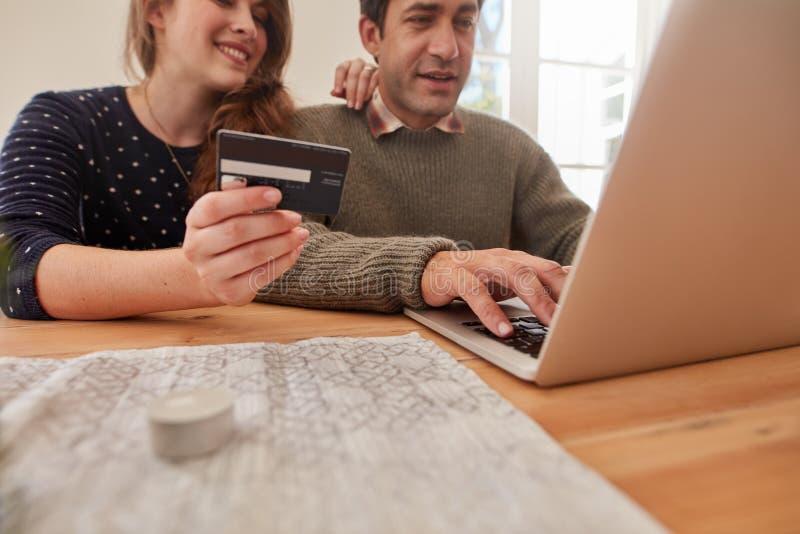 在家在网上购物与信用卡的年轻夫妇 免版税图库摄影