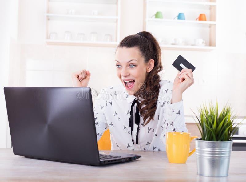 在家在网上购物激动的妇女 库存图片