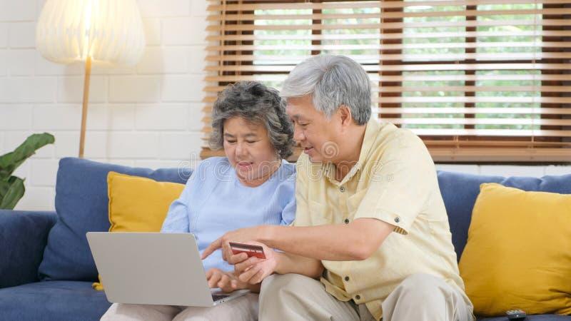 在家在网上购物通过使用手提电脑和信用卡客厅,退休人技术的资深亚洲夫妇 免版税库存图片