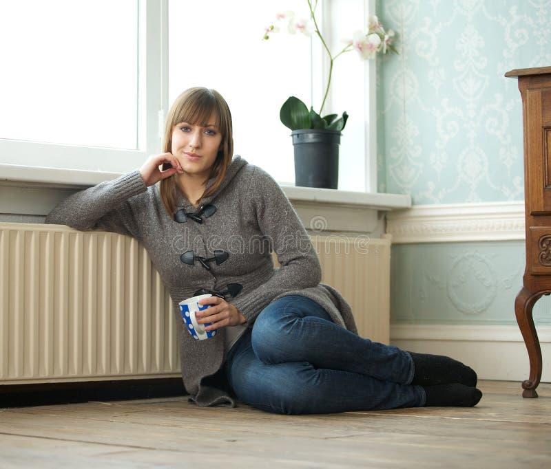 在家坐与一杯茶的少妇 免版税库存图片