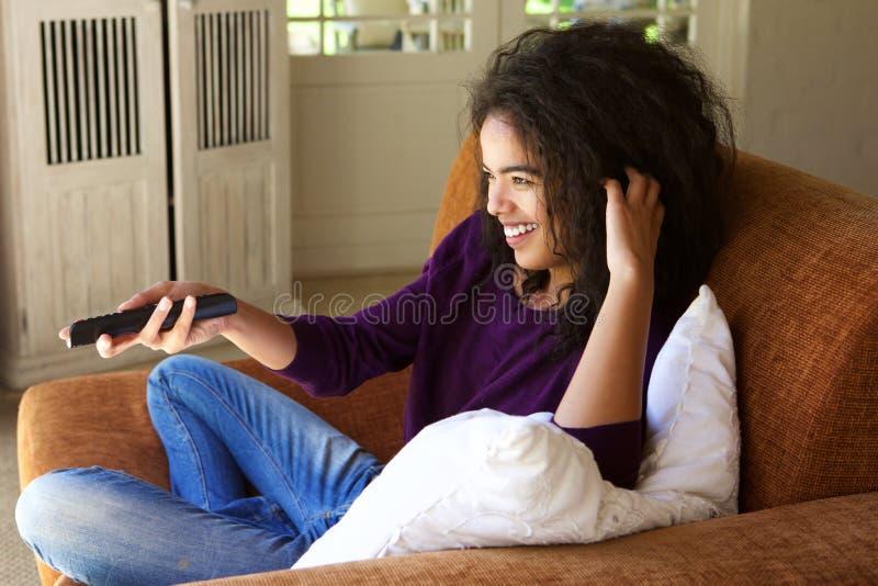 在家坐与遥控观看的电视的妇女 免版税库存照片