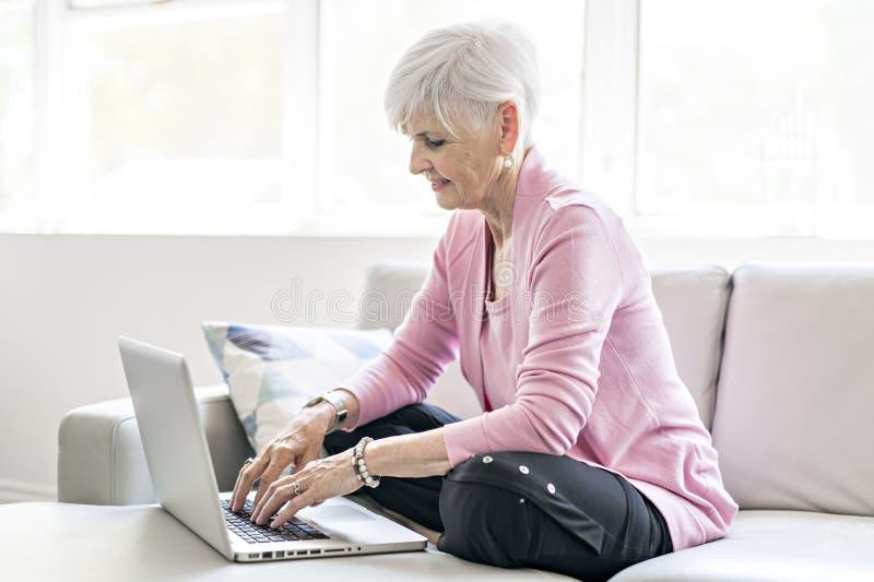 在家坐使用她的膝上型计算机的退休的资深妇女 库存照片