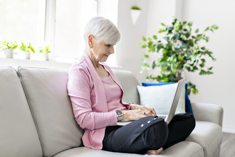在家坐使用她的膝上型计算机的退休的资深妇女 库存图片