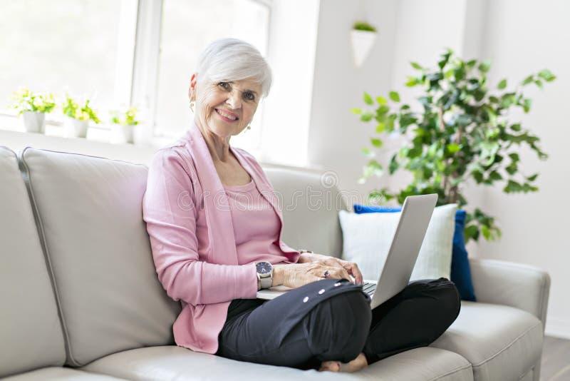 在家坐使用她的膝上型计算机的退休的资深妇女 图库摄影